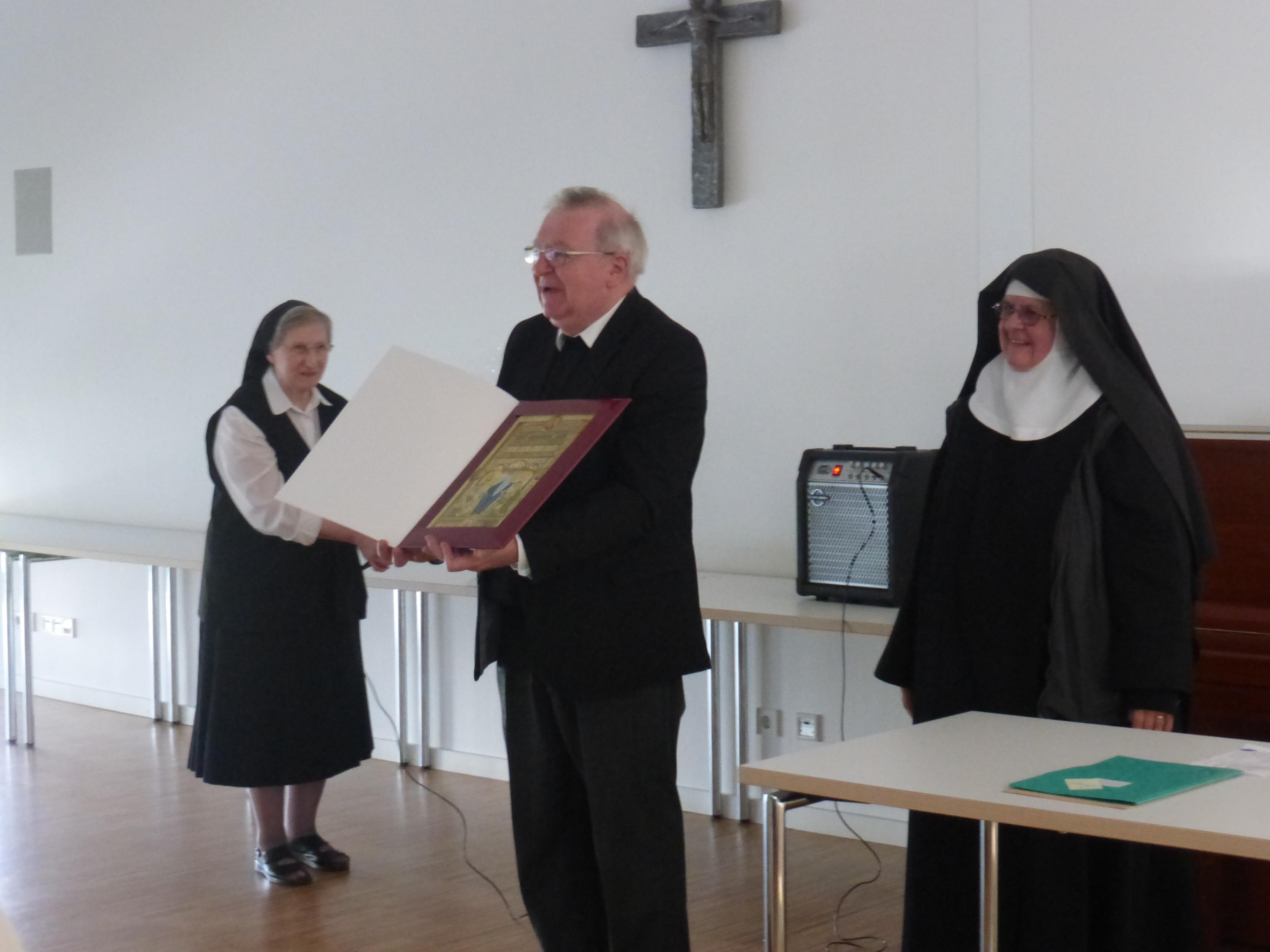 Weihbischof Otto Georgens zeigt das Geschenk für Schwester Johann Domek OSB.